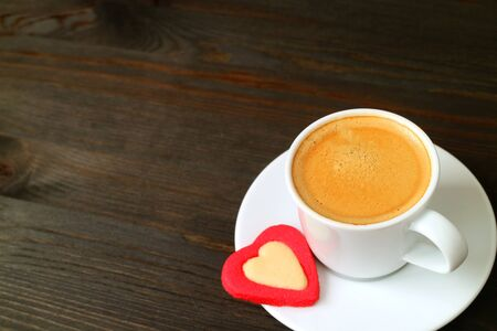 One cup of hot espresso coffee with a heart shaped cookie on dark brown wooden table with copy space