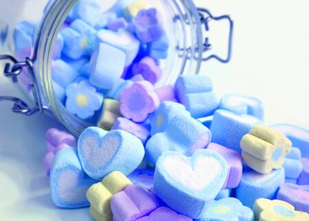Pastel Blue and Purple Color Heart and Flower Shaped Marshmallow Candies Scattered from Glass Jar onto White Table Stock Photo