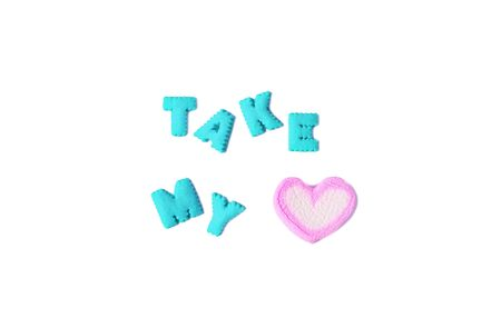 The Word TAKE MY HEART spelled with aqua blue alphabet shaped cookies and a heart shaped marshmallow candy on white background