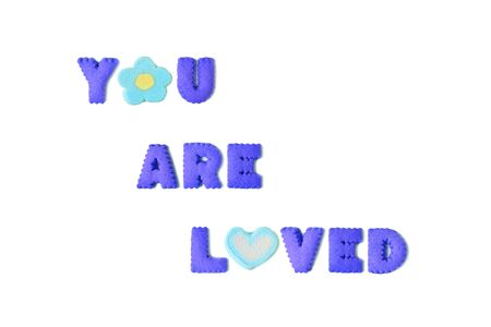 The word YOU ARE LOVED spelled with vivid blue alphabet shaped cookies and marshmallow candies on white background Stock Photo