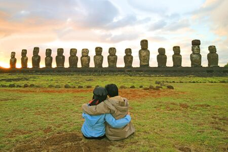 Couple having a happy moment in front of the awesome Moai statues of Ahu Tongariki at sunrise, Easter Island, Chile