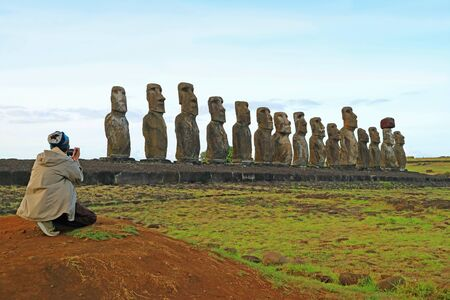 Man photographing the 15 huge Moai statues of Ahu Tongariki, Archaeological site in Easter Island, Chile, South America Stock Photo