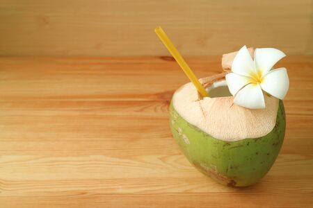 Fresh young coconut water in coconut shell with Plumeria flower on wooden table