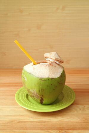 Fresh young coconut with yellow straw on a green plate ready for drinking