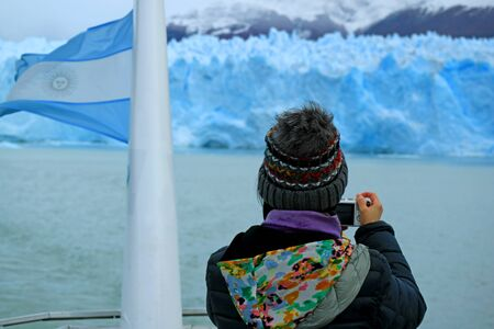 Female Tourist taking Photos of the Awesome Glacier Wall