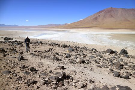 Man visiting Laguna Verde or the Green Lake, a popular destination in Potosi department of Bolivia, South America