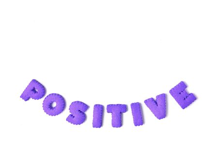 The word POSITIVE spelled with purple color alphabet shaped cookies on white background