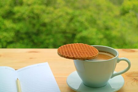 Cup of hot coffee with a stroopwafel placed on its top served on window side table against blurry green foliage