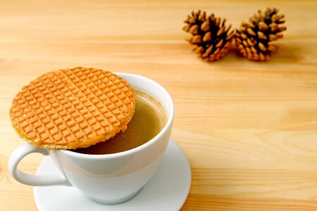 Stroopwafel Dutch Cookie Placed on Hot Coffee Cup Served on Wooden Table with Blurred Natural Pine Cones in Background