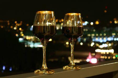 Dos copas de vino en el balcón con vista nocturna de la ciudad borrosa en el fondo Foto de archivo