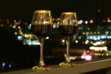 Two Wine Glasses on the Balcony with Blurry City Night View in the Background Фото со стока