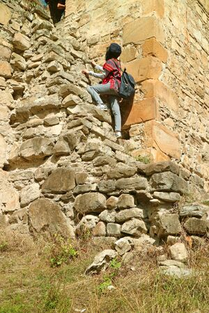 Visitor climbing up to the Sheupovari tower inside the Ananuri medieval castle complex, Georgia