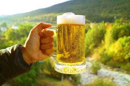 Man's hand holding a pint of beer against blurry foothill forest view in evening sunlight
