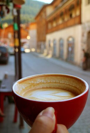 Closeup Texture of Half Cup of Hot Cappuccino Coffee in Womans Hand against Blurry Old Town