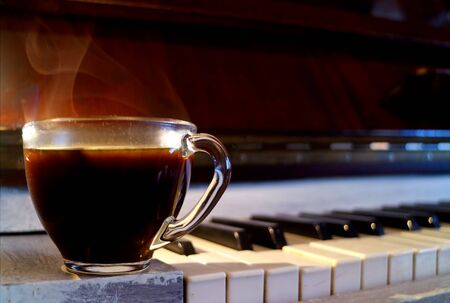 Closeup a cup of hot black coffee with smoke on the piano