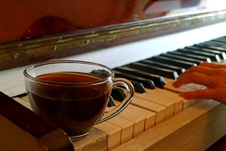 Cup of hot coffee on the piano with blurry pianists hand in background 写真素材