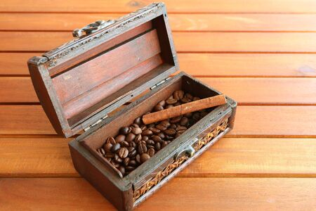 Roasted coffee beans with cinnamon stick in a wooden box isolated on wooden table Фото со стока