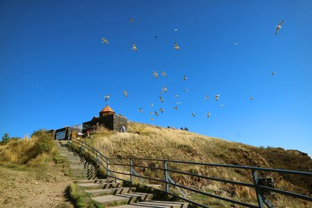 Stairs Leading to Sevanavank Monastery and a Large Group of Flying Seagulls in Blue Sky, Sevan Peninsula in Armenia Stock Photo