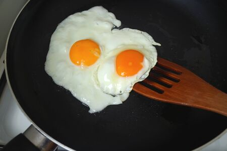 Pair of chicken eggs being fried in a fry pan