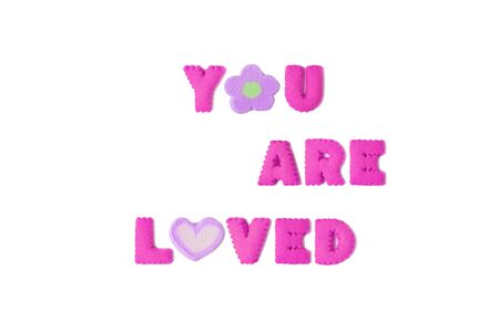 The word YOU ARE LOVED spelled with vivid pink alphabet cookies and purple marshmallow on white background