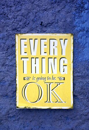 Message of EVERYTHING is going to be OK on the yellow board hanging on the rough blue wall