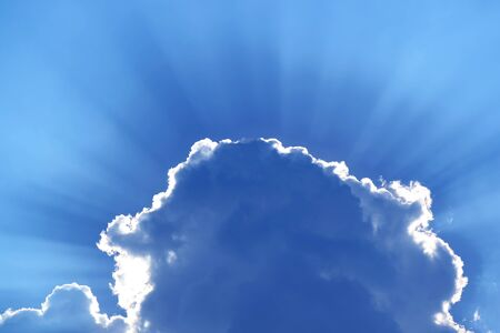 Stunning blue grey cumulus cloud with sunbeams in the backdrop