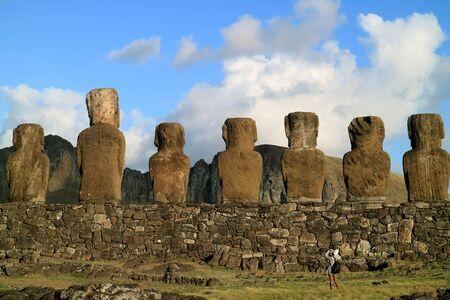 Female traveler photographing the back of gigantic Moai statues at Ahu Tongariki ceremonial platform on Easter Island, Chile
