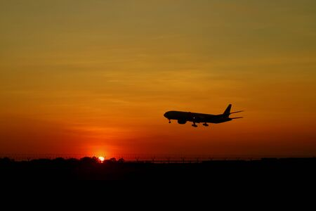 Silhouette of airplane flying on the beautiful sunrise sky