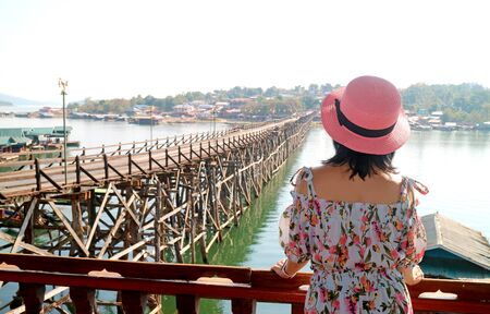 Woman in Pink Hat Admiring the Mon Bridge, stunning Landmark of Sangkhlaburi District, Thailand