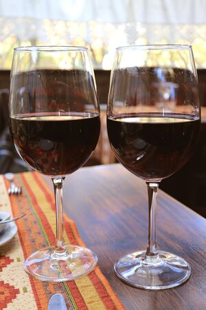 Vertical image of two glasses of red wine on the table in restaurant