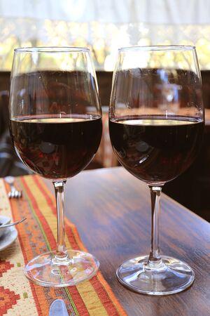 Vertikales Bild von zwei Gläsern Rotwein auf dem Tisch im Restaurant