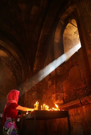 Natural sunlight shining into a medieval church of a woman lighting candles