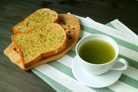 Closeup a Cup of Hot Green Tea with Garlic Butter Toasts on White and Green Napkin