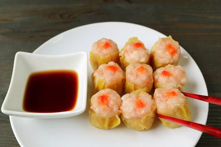 Red Chopsticks Picking Up a Shumai or Shrimp and Pork Filled Chinese Steamed Dumpling