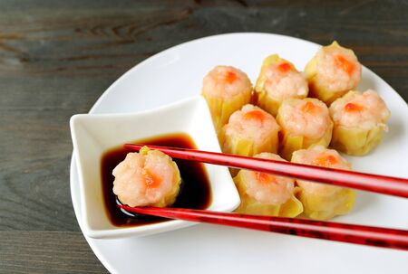 Dipping Shrimp and Pork Filled Chinese Steamed Dumpling in Soy-vinegar Sauce