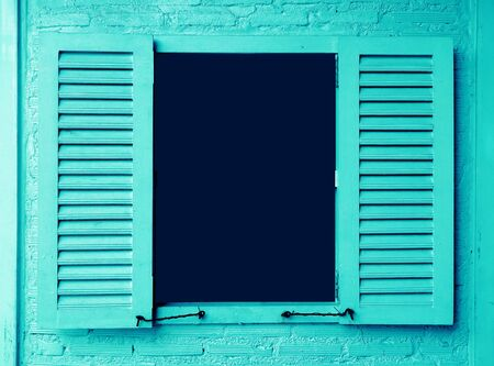 Ice blue colored wooden window with shutters on brick wall 版權商用圖片