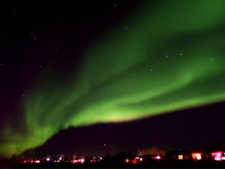 Spectacular northern lights flashing over a small town of northern Iceland Imagens