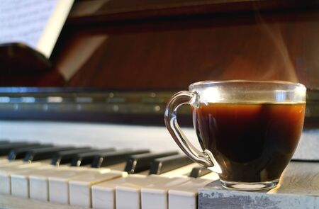 Cup of hot coffee with smoke with blurry piano's keyboard in background Stock Photo