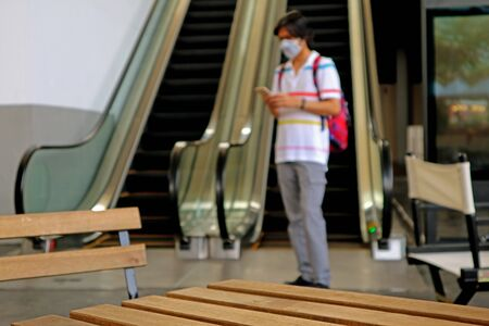 Closeup empty wooden table with blurry man wearing face mask protects against flu