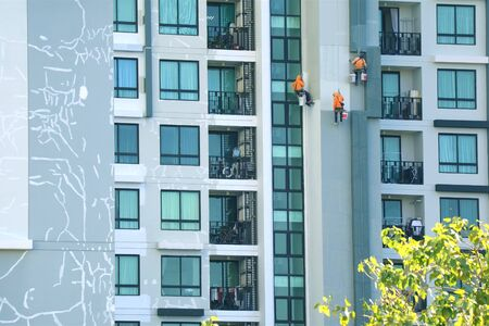 Three rope access workers painting the facade of a high modern building