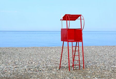 Vibrant red lifeguard chair on the empty beach