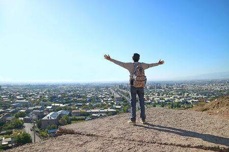 Young man standing on the edge of the hill opening arms with the impressive city aerial view