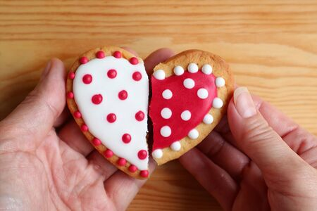Man's hand and woman's hand holding two half heart shaped cookies attach on wooden background Stock Photo