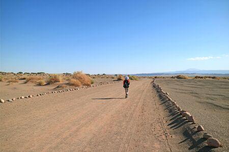 Female Traveler Walking on the Desert Road of Aldea de Tulor Archaeological Site, Atacama Desert, Northern Chile, South America