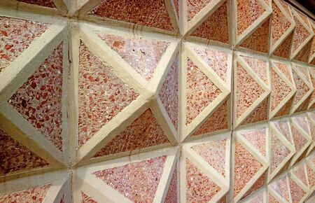 Diminishing perspective of a 3D geometric patterned concrete with red stones wall Stock fotó