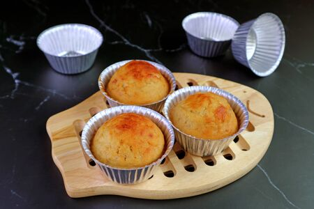 Homemade Banana Muffins in Mold on Wooden Bread Board with Empty Aluminum Muffin Mold on Kitchen's Black Marble Table