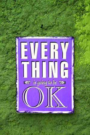 Pop art style purple signboard of EVERYTHING is going to be OK on the rough green wall Archivio Fotografico