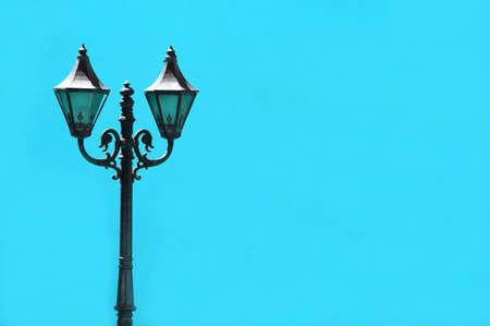 Cast iron antique lamppost against vibrant sky blue colored concrete wall