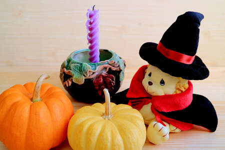 Adorable lion toy in wizard costume with two mini pumpkins and a candle with holder on wooden table Stock Photo