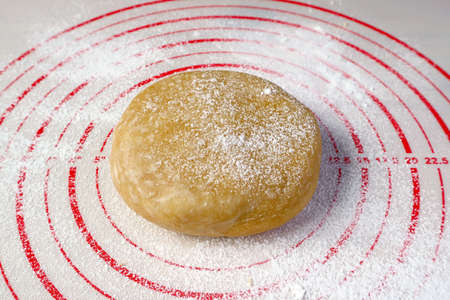 Pie dough isolated on a baking mat for the concept of baking at home Imagens